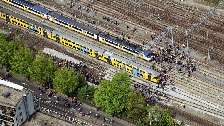 Bezoekers van Koninginnedag liepen vorig jaar over het spoor bij Centraal Station Amsterdam. Beeld ANP