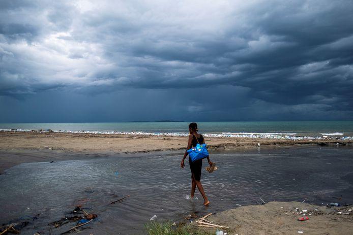 Een vrouw loopt in Les Cayes door een plas water vol puin van de aardbeving, terwijl tropische storm Grace in de achtergrond nadert.