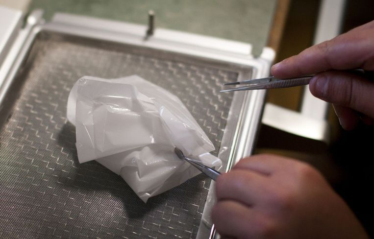 Munday vouwt met twee pincetten de met stof ¿ en hopelijk ook bacteriën ¿ bedekte filters dicht. Beeld Ronald Veldhuizen