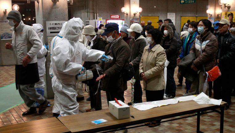 Evacuées worden getest op straling. Beeld ap