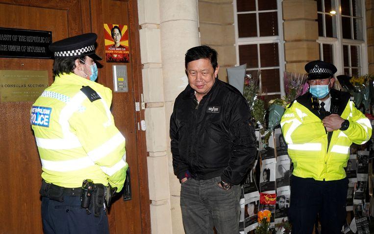 Kyaw Zwar Minn, de ambassadeur van Myanmar in het Verenigd Koninkrijk, staat met twee agenten voor het ambassadegebouw in Londen, waar hij niet langer in mag. Beeld AFP