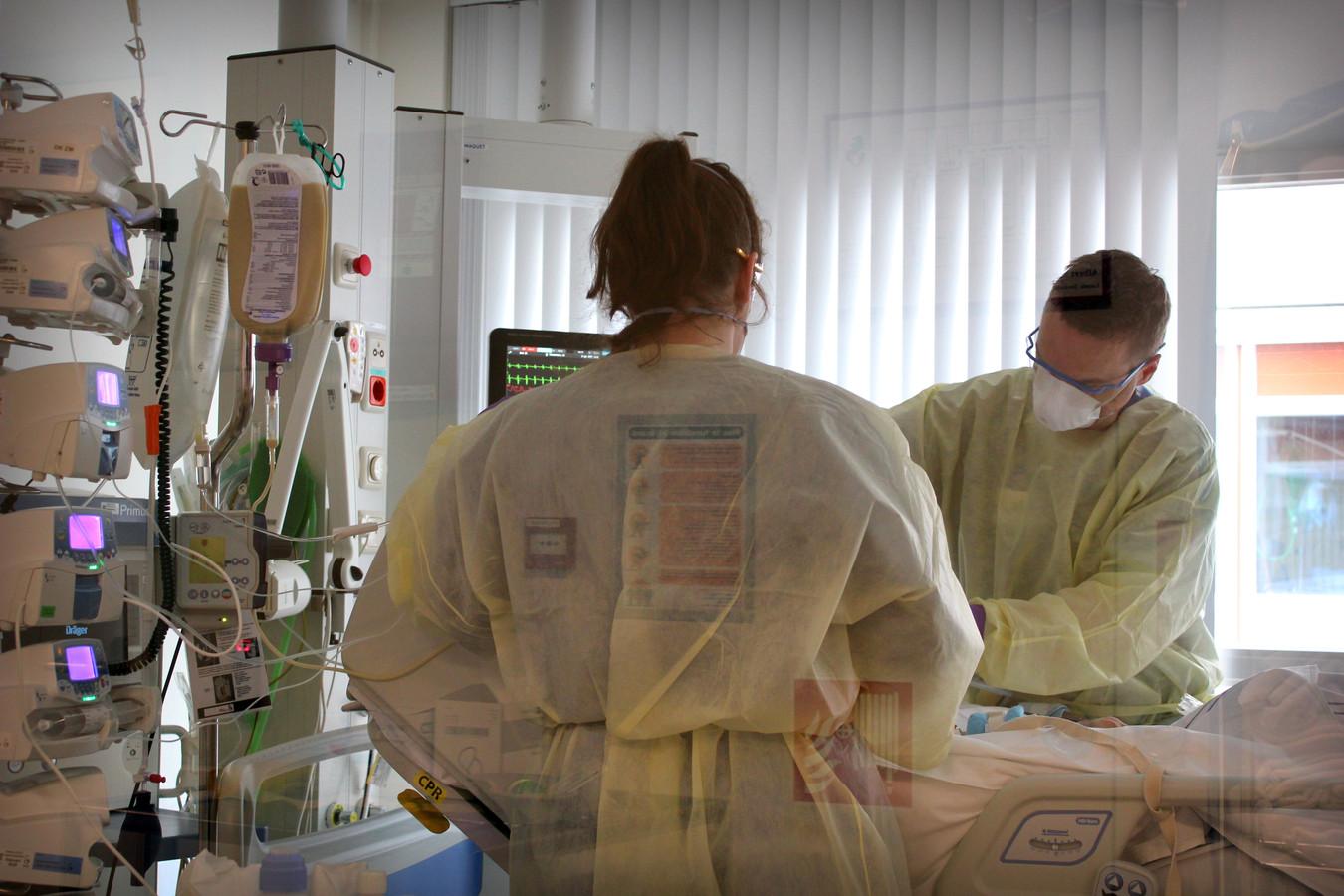 Twee verpleegkundigen in een ic-kamer. De kamers zijn afgesloten; daarom is de foto vanaf de gang en door het glas gemaakt.