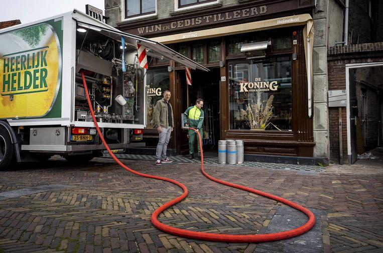 Een verse lading bier komt aan bij café De Koning in Alkmaar. Binnenkort zal het gerstenat weer rijkelijk vloeien - op het terras.  Beeld ANP