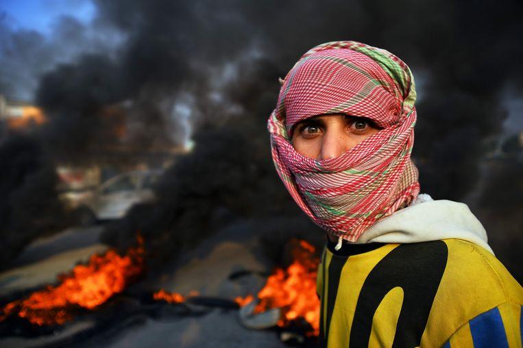 Een jonge demonstrant in de Iraakse stad Najaf, met op de achtergrond brandende autobanden. Beeld AFP