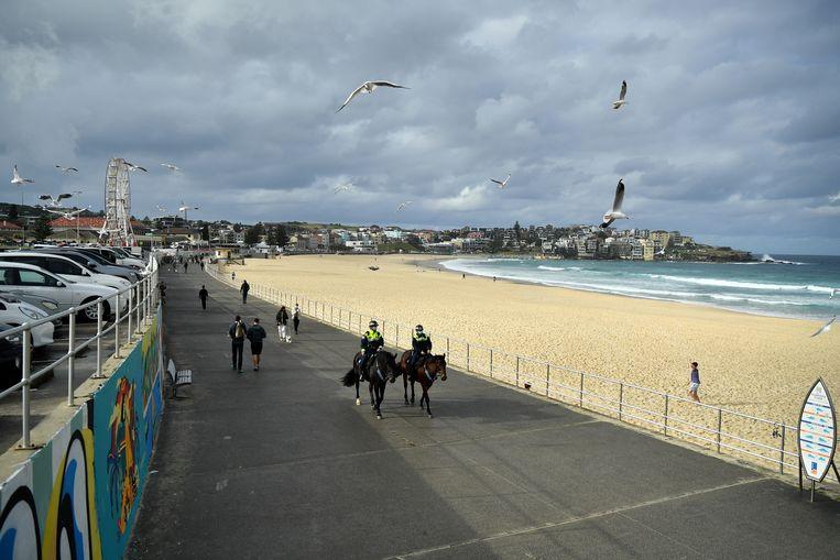 Politie patrouilleert op het strand in Sydney. Dit weekend werd een zware lockdown van twee weken aangekondigd. Beeld EPA