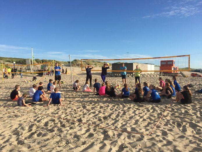 Beachvolleyballers uit de eredivisie Mexime van Driel en Katja Stam geven een clinic op het strand van Ter Heijde aan jeugdleden van volleybalvereniging Monza. Trainers van de club kijken toe.