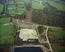 Luchtfoto van 16 oktober 1982, van de aanleg van de A27 ten zuidoosten van Utrecht, met op de voorgrond het toekomstige spoorviaduct in de spoorlijn Utrecht-Arnhem, in het midden een zandzuiger in het in te graven tracé voor de rijksweg en daarachter de tijdelijk omgelegde Koningsweg. Op de achtergrond het landgoed Amelisweerd met het uitgekapte tracé voor de weg.