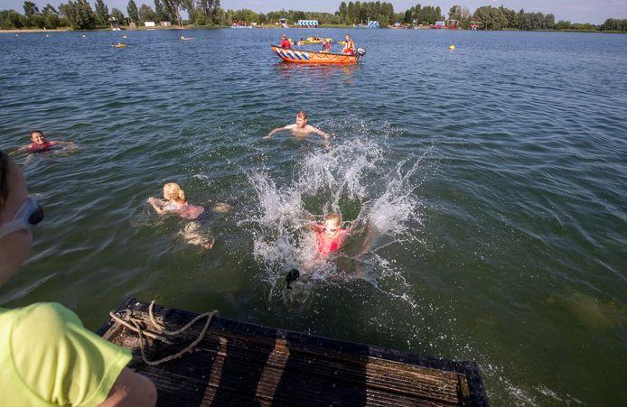 Kinderen leren zwemmen in open water in Zoelen.