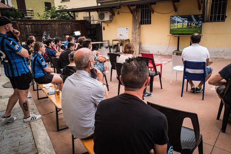 Supporters van Atalanta volgen donderdag de met 2-0-gewonnen wedstrijd tegen Napoli in de binnenplaats van supportersbar Zini. Beeld Nicola Zolin