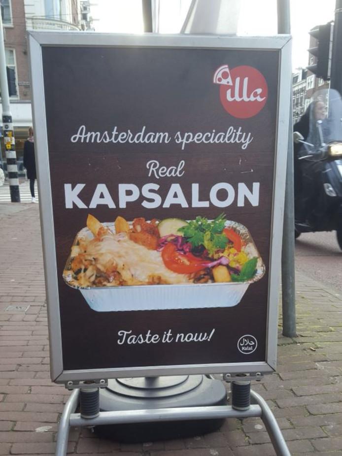 Het bord waarop de shoarmazaak claimt dat de kapsalon een Amsterdamse oorsprong heeft.