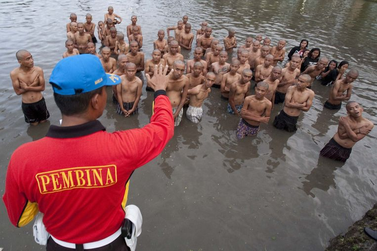 In this photograph taken on December 13, 2011 a police officer gives instruction to a group of detained Indonesian punks in a lake after their hair was shaved off at a police school in Aceh Besar in Aceh province. Sharia police are
