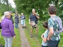 Tijdens de wandeling ter ere van het 65-jarig bestaan van De Steltkluut heeft gids Guy de Vos (korte broek) veel aandacht voor de invasieve soorten. Hier toont toont hij de Amerikaanse vogelkers.
