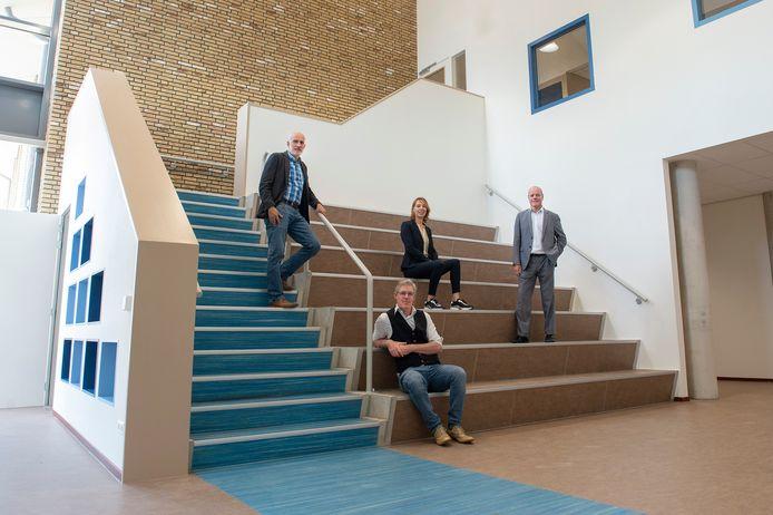 Peter Kraak, Barry Hellings, Anouk van Lange en Johan van Knijff op de trap en tribune in de ruimte waar straks bijvoorbeeld voorgelezen kan worden aan een groep of voorstellingen gehouden kunnen worden.