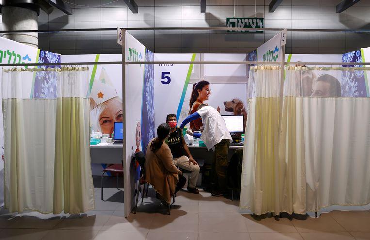 In het voetbalstadion van de Israëlische kustplaats Netanja krijgen inwoners van de stad woensdag het Pfizer-vaccin toegediend.  Beeld AFP