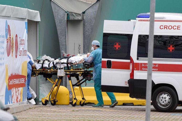 Een patiënt wordt binnengebracht in het San Raffaele-ziekenhuis in Milaan (in maart).  Beeld Photo News