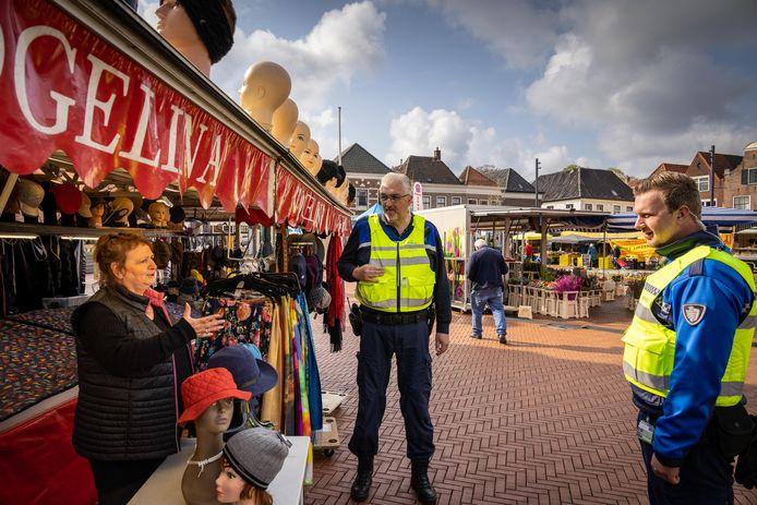 """Lientje Muller wordt na vier maanden afwezigheid op de weekmarkt van Steenwijk welkom geheten door marktmeesters en gemeentelijk toezichthouders Jackie Mondria (links) en Lars Dijsselhof. Lientje, over de afwezigheid: ,,Het was frustrerend. Want lieverd, ik sta hier al zo lang."""""""