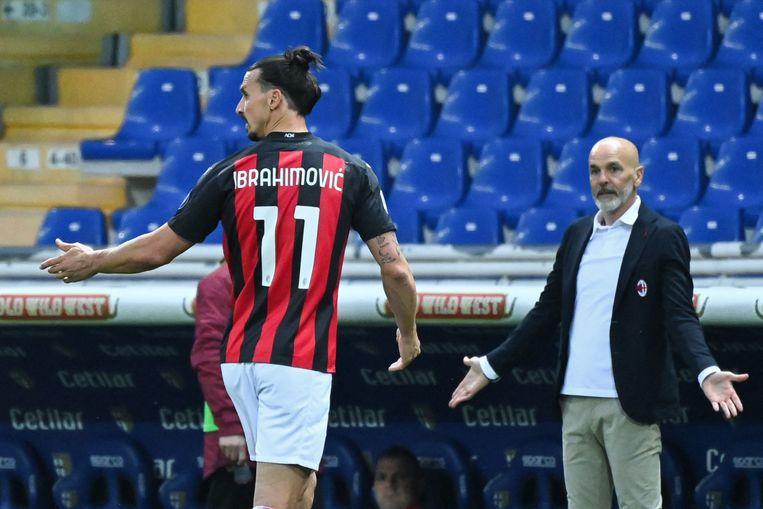 Zlatan Ibrahimovic overlegt met zijn trainer Stefano Pioli. Beeld AFP