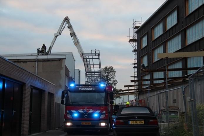 Met een hoogwerker blust een brandweerman het vuur.