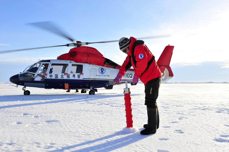 Een lid van de vierde Chinese wetenschappelijke expeditie naar de Noordpool neemt een monster uit het ijs. Beeld Belga