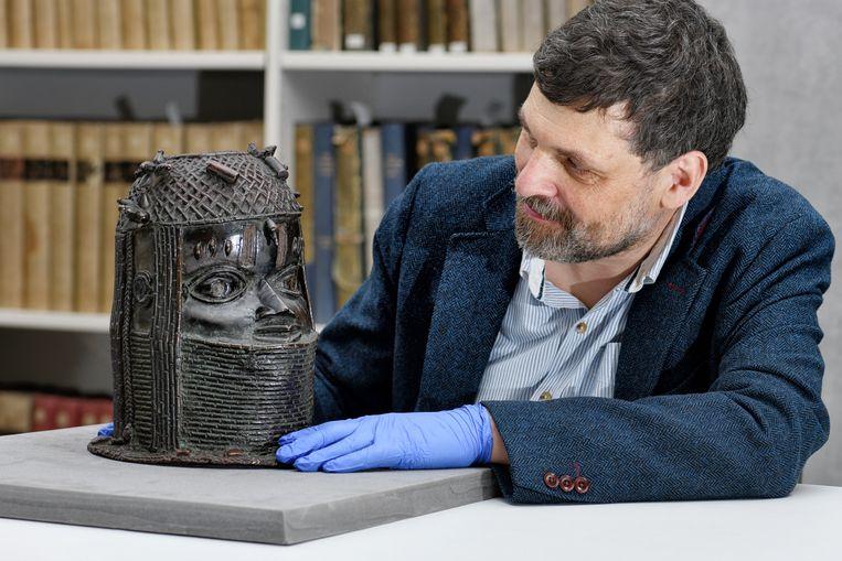 Neil Curtis, Head of Museums and Special collections, laat het hoofd van de Oba, ofwel koning, zien in The Sir Duncan Rice Library in Aberdeen. Beeld REUTERS