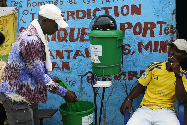 Inwoners van Guinee wassen hun handen met chloorwater. Beeld ap