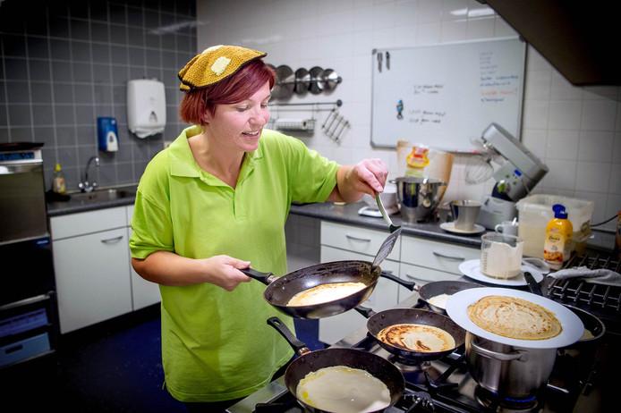 Mireille Roelofs is druk bezig met het bakken van pannenkoeken tijdens de editie van Sint  Pannenkoek in 2017.