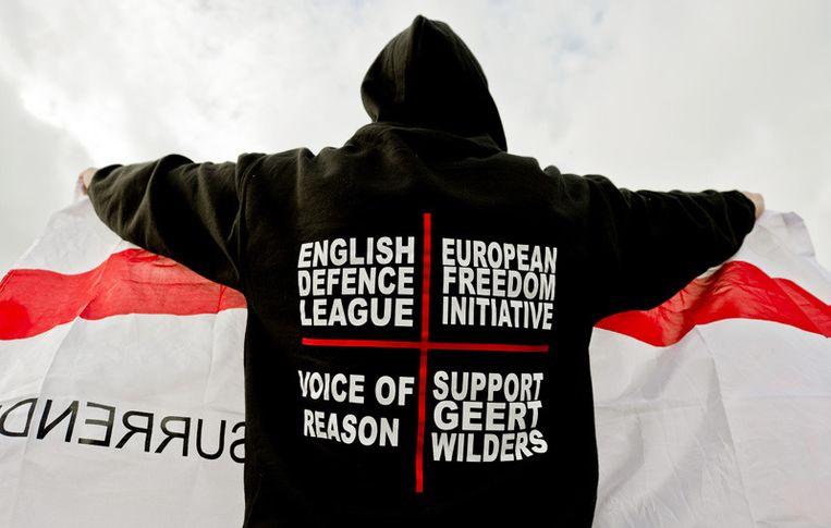 Een lid van de English Defence League toont zaterdag een vlag aan de media. Foto © Koen van Weel/anp Beeld