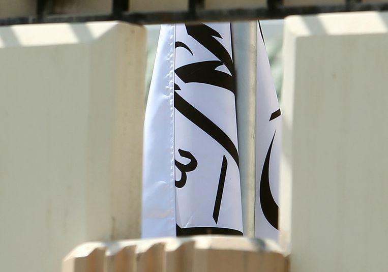 Door een muur is een stukje zichtbaar van de gewraakte vlag in het kantoor van de Taliban in Doha, Qatar. Beeld AP
