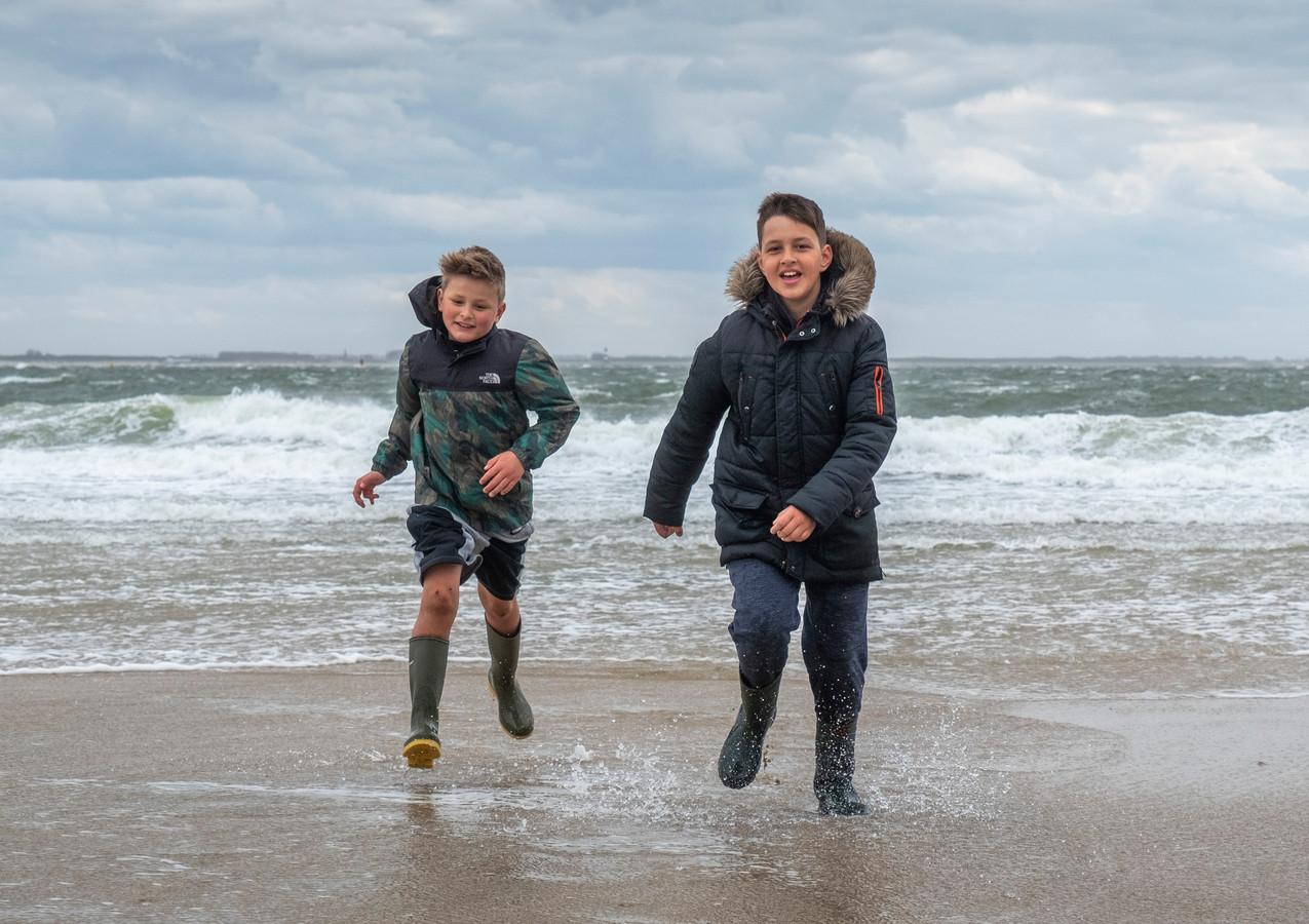 """Don (9, links) en Sem (10) genieten van de harde wind op het badstrand in Vlissingen. Koud? Don heeft het nooit koud. Boven zijn groene laarzen draagt hij een korte broek. ,,Dat doe ik altijd. Zit gewoon lekker."""""""