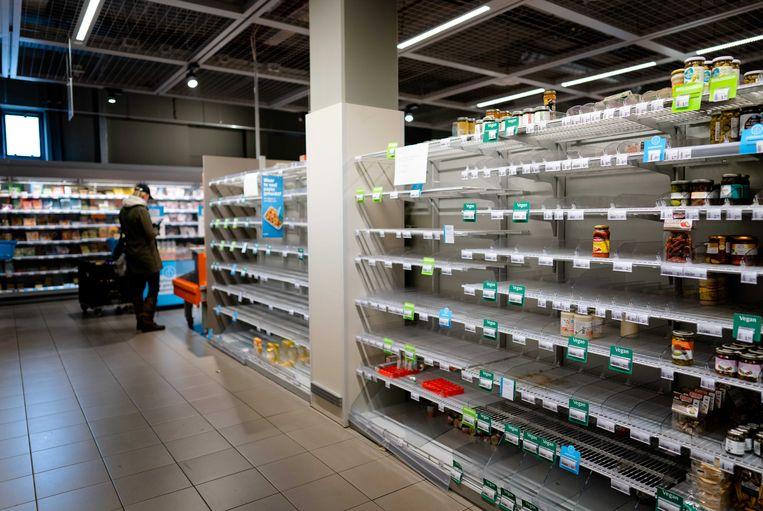 Lege schappen bij een filiaal van Albert Heijn in Amsterdam. Vooral pasta, wc-papier en groenteconserven worden ingeslagen. Beeld ANP