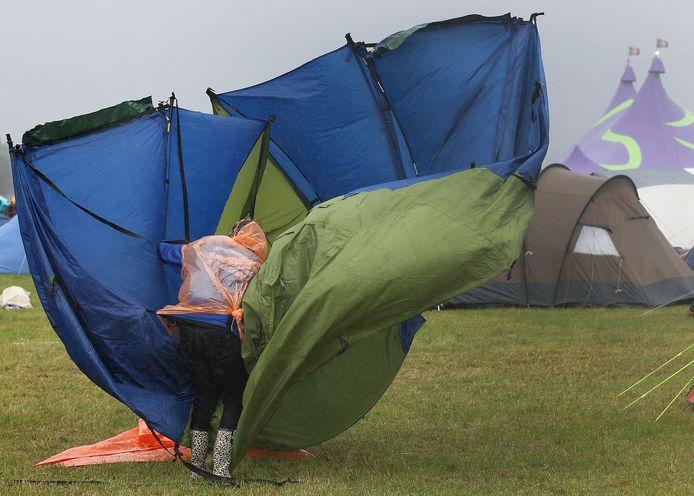 Een campinggast laat zich door de hevige wind niet tegenhouden bij het opzetten van de tent op de Zwarte Cross. Archieffoto.
