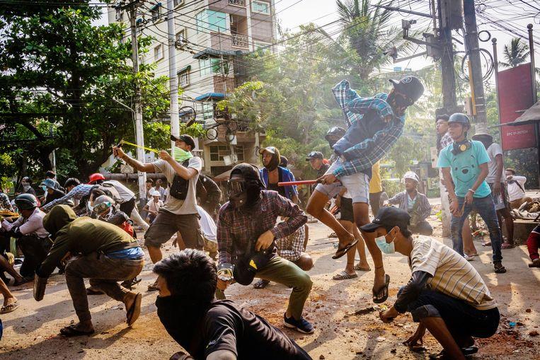 Demonstraten gaan zondag de confrontatie aan met veiligheidstroepen in Yangon, de grootste stad van Myanmar. Beeld Getty