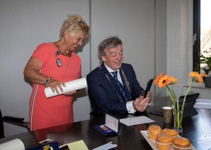 Waarnemend Burgemeester Fons Naterop (rechts, samen met Ineke Bouwens) belt in 2020 met een inwoner die op Koningsdag een Koninklijke Onderscheiding heeft gekregen. Het ziet er naar uit dat hij als waarnemer nog zeker twee keer lintjes mag uitdelen in Kapelle.