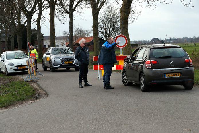 Een auto wordt weggestuurd bij de ingang van de Noorder Markweg in Loerbeek. De weg is door de gemeente afgesloten omdat het zo druk was bij hondenopvang Zalikas in de straat, dat het risico op verspreiding van het corona virus te groot werd.