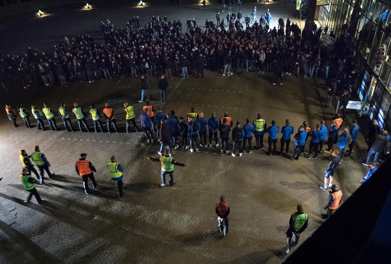 Stewards houden de supporters van de Graafschap op afstand voordat de spelersbus bij het stadion arriveert na de wedstrijd vrijdagavond tegen Jong Ajax.