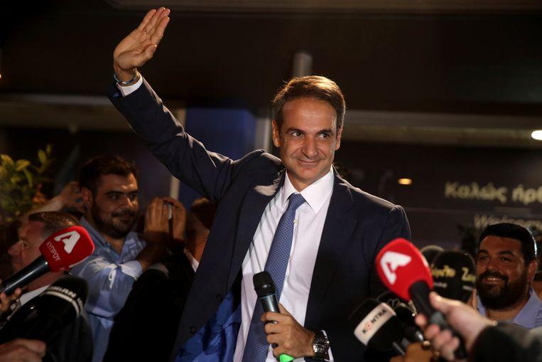 Kyriakos Mitsotakis zwaait zijn aanhangers toe in Athene als blijkt dat zijn partij Nieuwe Democratie de verkiezingen heeft gewonnen.  Beeld AP