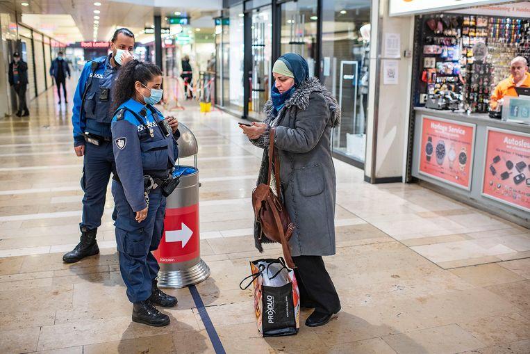 Een vrouw in winkelcentrum Zuidplein laat op haar smartphone zien dat zij een medische indicatie heeft om geen mondkapje te hoeven dragen. Beeld Guus Dubbelman / de Volkskrant