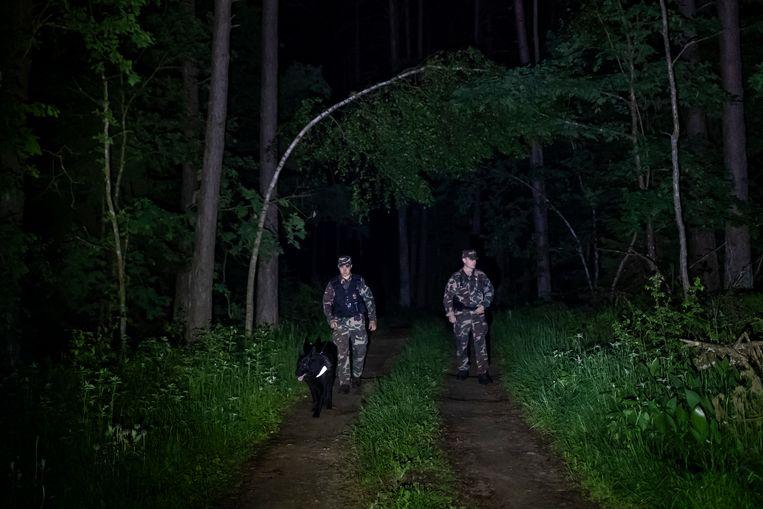 Leden van de Litouwse grenswacht patrouilleren aan de grens met Wit-Rusland, in de buurt van het stadje Kapciamiestis, zo'n 160 km van de hoofdstad Vilnius. Beeld AP