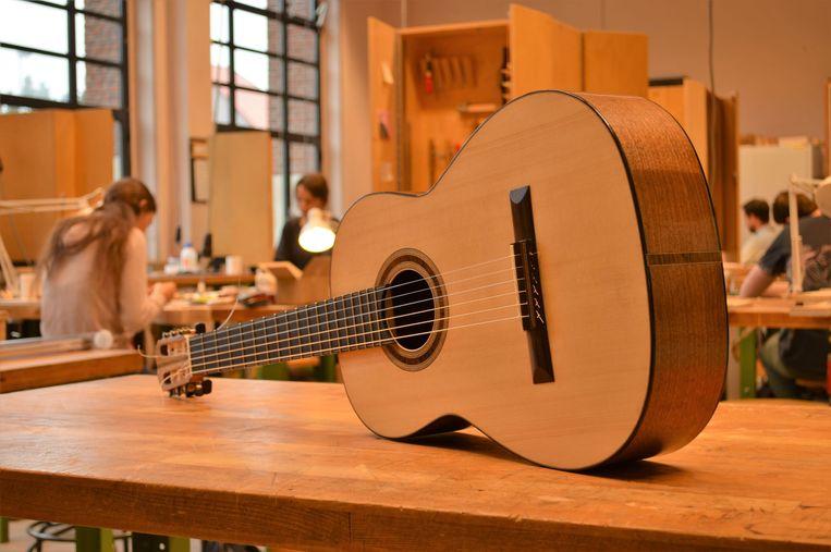 De studenten maakt een gitaar uit inheems hout.