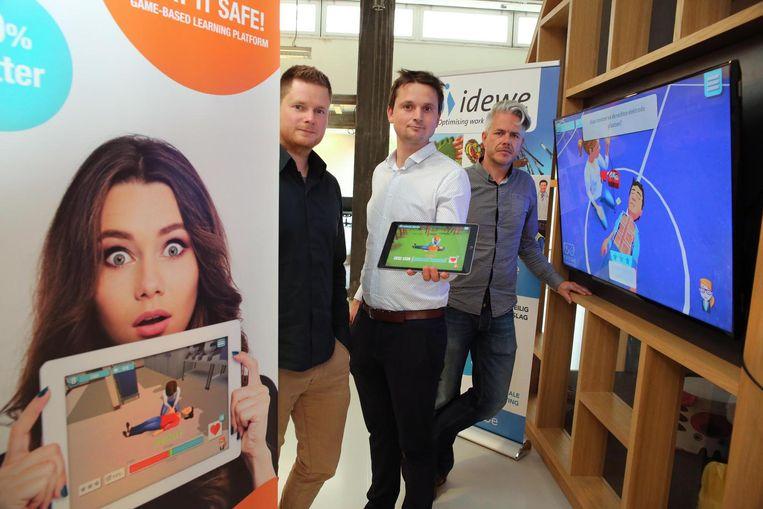 Brecht Kets (links) en Mike Ptacek (recht) van het Kortrijkse bedrijf Greygin en schepen Arne Vandendriessche met de app Play it Safe.