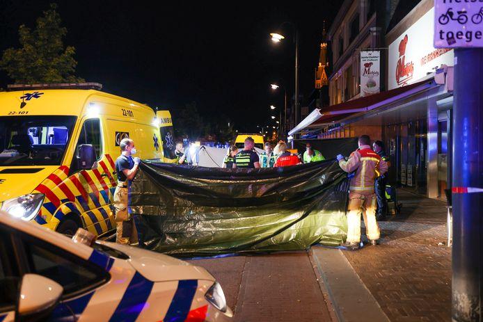 Hulpverleners proberen op de Woenselse Markt het ontzielde lichaam van een man buiten het zicht van geschokt publiek te houden.