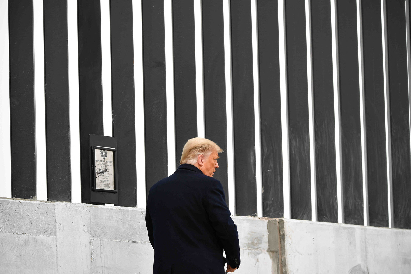 Donald Trump bezoekt in januari van dit jaar een stukje van de grensmuur die hij liet bouwen.