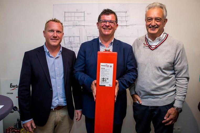 Minister Tommelein toont een van de batterijen die in het appartementsgebouw geplaatst zullen worden. Naast hem projectleider Nick Verwimp en ingenieur Marc Van Goidenhoven.