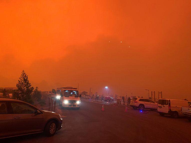 De lucht kleurt rood in Mallacoota, waar zo'n vierduizend mensen zich aan het strand hebben verzameld. Beeld via REUTERS