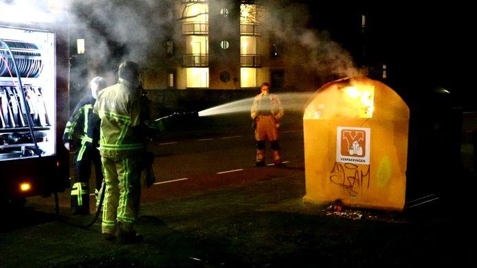 De brandweer blust de container aan de Floraparkstraat.