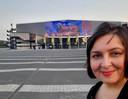 De Roosendaalse kunstenaar Erika Stanley poseert voor Ahoy in Rotterdam. Op de led-facade is haar schilderij van de kubuswoningen te zien.