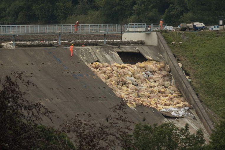 400 zakken van elke duizend kilo vol zand, gravel en stenen zijn gestapeld bij de zwakke plek van de dam. Beeld AFP
