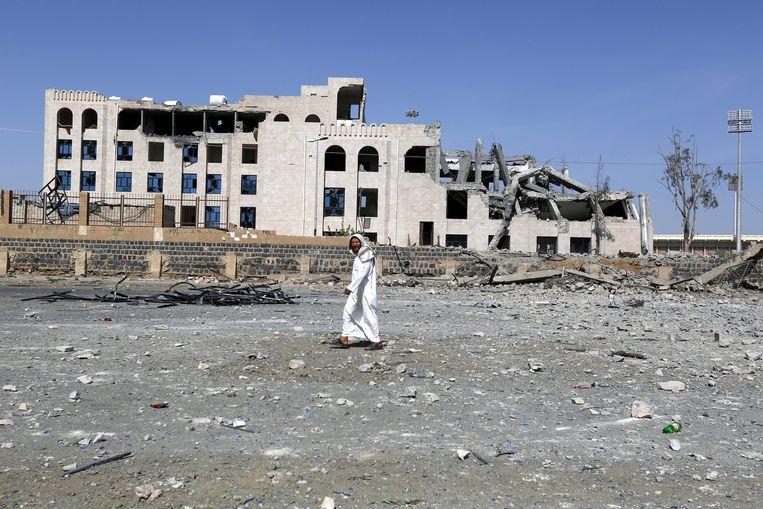 Een Jemeniet loopt langs een gebouw dat zwaar beschadigd is door een luchtaanval. Beeld epa