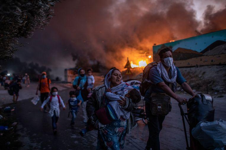 Vluchtelingen ontvluchten de brand in kamp Moria.  Beeld AP