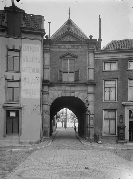 De Sabelspoort gezien vanaf de Grote Markt in 1920. Links de handel in aardewerk, glas en porselein van Johan Willems. Rechts het toenmalige hulppostkantoor. Midden in het beeld een van de vele zendmasten voor draadloze telefonie en telegrafie, waar Arnhem in die tijd vol mee stond.